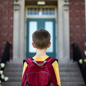 boy with backpack facing schoolforweb