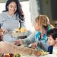 Volunteer serving healthy meal to families in food bank